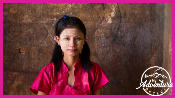 Woman in pink dress wearing thanaka paste on her face